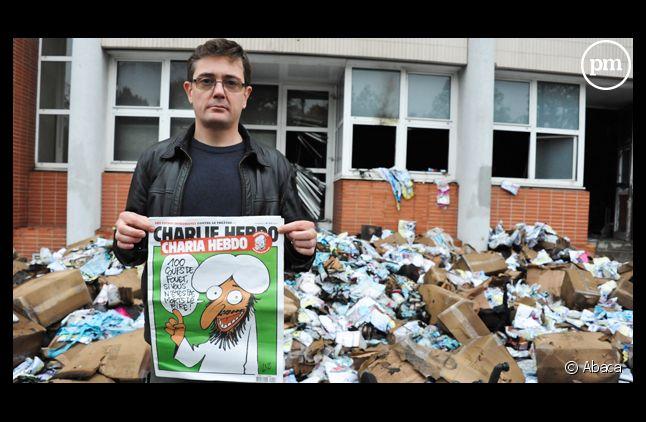 """Charb, directeur de la rédaction de """"Charlie Hebdo"""" devant les locaux du journal, dévastés par un incendie criminel."""
